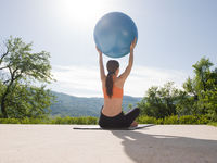 woman doing exercise with pilates ball