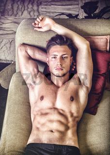 Topless young man on sofa