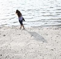 young women walk on seashore. Full body rear shot