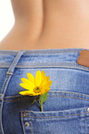 Yellow flower in a pocket female jeans