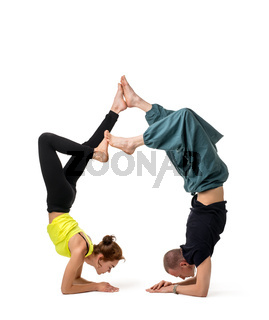 Two girls doing yoga together isolated on white