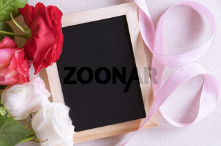 Blank blackboard and roses with ribbon
