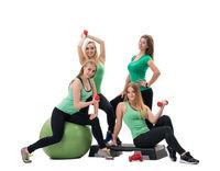 Pretty sportswomen in green tops with dumbbells