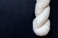 skein of natural white yarn with black slate background