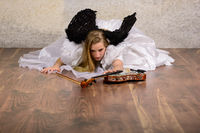 Young blond woman in wedding dress with black wings lies on the floor and reaches for a violin