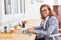 Kreativer junger Mann als Nerd am Laptop