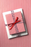 Top view of a Christmas present wrapped with red striped paper on a background of the same paper.
