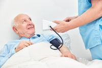 Krankenschwester beim Blutdruck messen von Senior