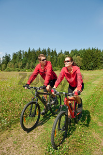 Young couple riding mountain bike in spring meadow