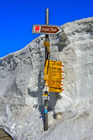 Wanderwegweiser und Wegweiser der Grand Tour of Switzerland im Schnee auf der St. Gotthard-Passhöhe