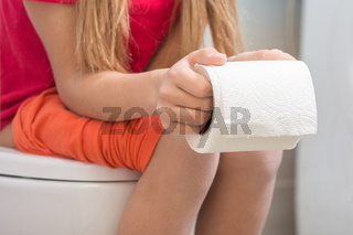 A girl is holding a roll of toilet paper in her hands, sitting on the toilet