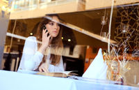 Young brunette talking by phone in a restaurant
