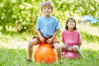 Junge und Mädchen hüpfen auf einem Ball
