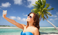 woman taking selfie by smartphone on beach