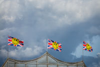 Three British flags with yellow smiley faces fluttering in a strong wind on a dark cloudy and rainy day