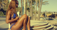 Happy African Girl in Bikini Sits at Beach Bench