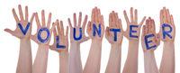 Word Volunteer On Hands, On White