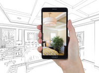 Hand Holding Smart Phone Displaying Photo of Bedroom Drawing Behind