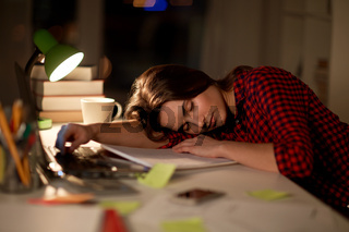 student or woman sleeping on table at night home