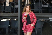 Young fashion woman in red tweed jacket and shorts suit at sidewalk cafe