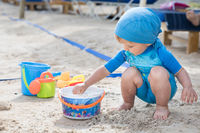 infant boy plays at the beach