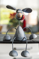 A metal mouse sits relaxed in front of the kitchen window