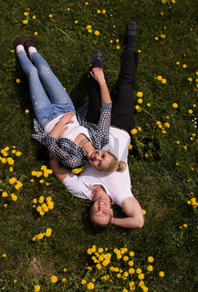 man and woman lying on the grass