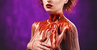 Young woman's body covered with a blood. Studio shot