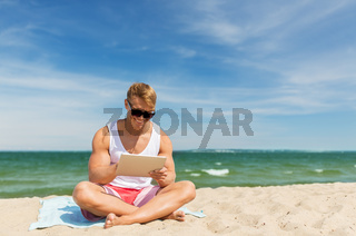 happy smiling young man with tablet pc on beach