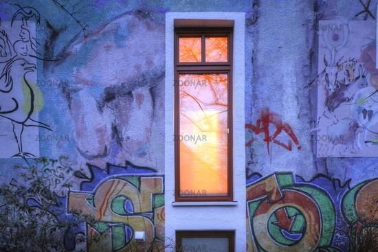 Beleuchtetes Fenster,  Hauswand  mit Graffiti  im  Ostertorviertel