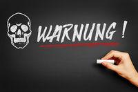 Hand schreibt Warnung an Tafel