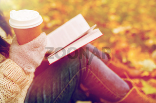 woman with book drinking coffee in autumn park