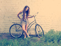 Sad girl with her urban bike standing near white wall and looking down at feet, retro looking instagram toned shot