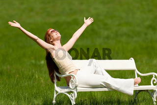 Red hair woman enjoying sun on white bench in spring