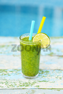 Freshly blended green fruit smoothie in glass with straw