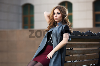 Sad young fashion woman with long curly hairs sitting on bench