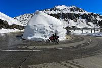 Motorradfahrer fährt in einer Haarnadekurvel um einen Schneekegel