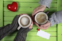 Young couple drinking hot coffee at wooden table on a date