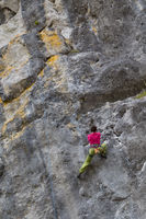 Strong girl climbs on a rock, doing sports climbing in nature.