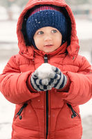 Sweet child in the snow with a snowball in his hands