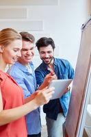 Start-Up Team mit Tablet freut sich über Lösung
