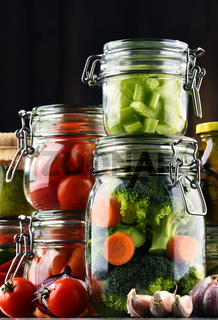 Jars with marinated food and organic raw vegetables.