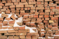 Pile of red bricks covered in winter snow with copyspace area.