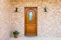 Stylish wooden front - entrance door in a detached house - embedded in a brick wall