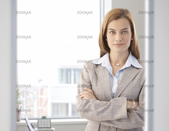 Confident businesswoman smiling in bright office