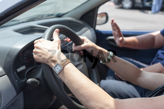 Senior learning to drive a car with a driving instructor