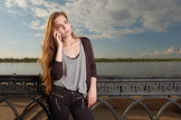 Pensive woman listening to the cell phone in front of waterfront fence