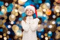 dreaming girl in santa helper hat over lights