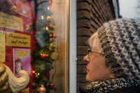 A lonely senior looks at the Christmas-decorated announcement of a dance school.
