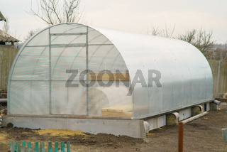 Greenhouse made of polycarbonate outside in the early spring.